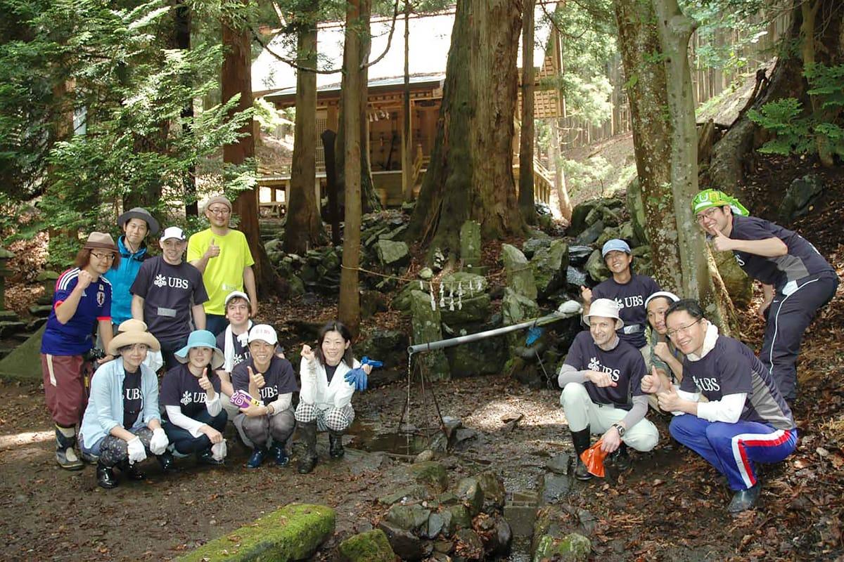 清掃後、きれいになった尾崎神社奥宮の池の前で笑顔を見せるUBSグループ社員と関係者