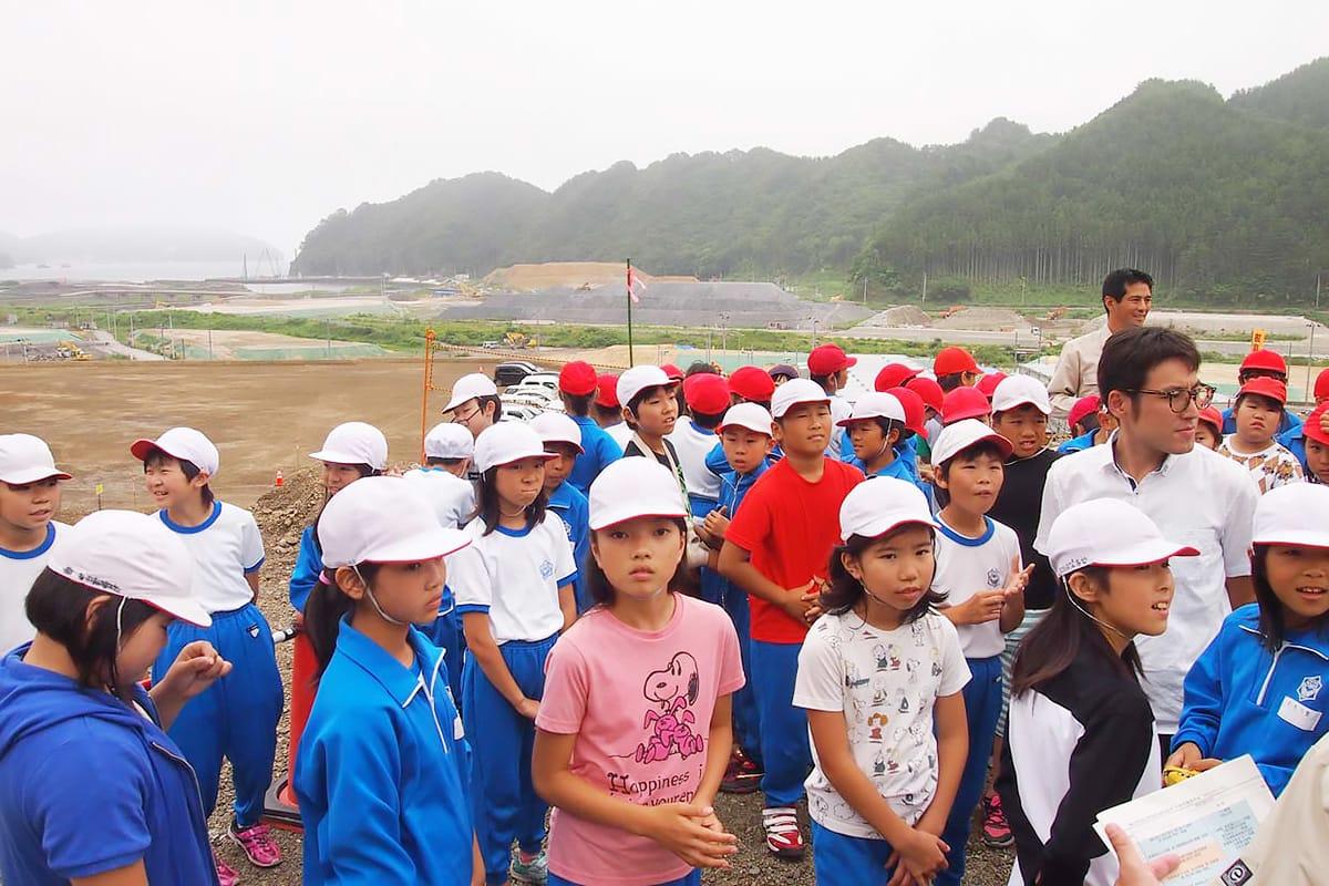 学校施設の建設現場を見学する児童ら