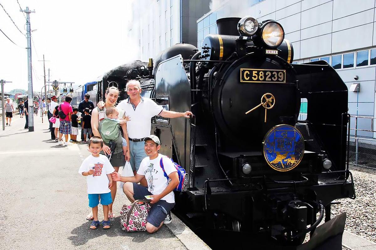 「SL銀河」をバックに笑顔で記念写真におさまる家族連れ=16日、釜石駅
