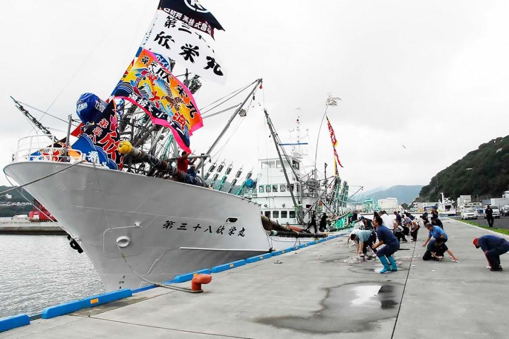 餅まきで出港を祝う浜幸水産の「第38欣栄丸」=17日午前10時50分、新浜町の魚市場で