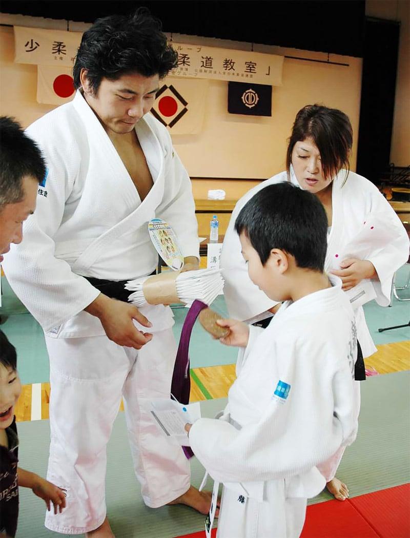 溝口さん(右)、西山さんから五輪メダルを見せてもらう子ども