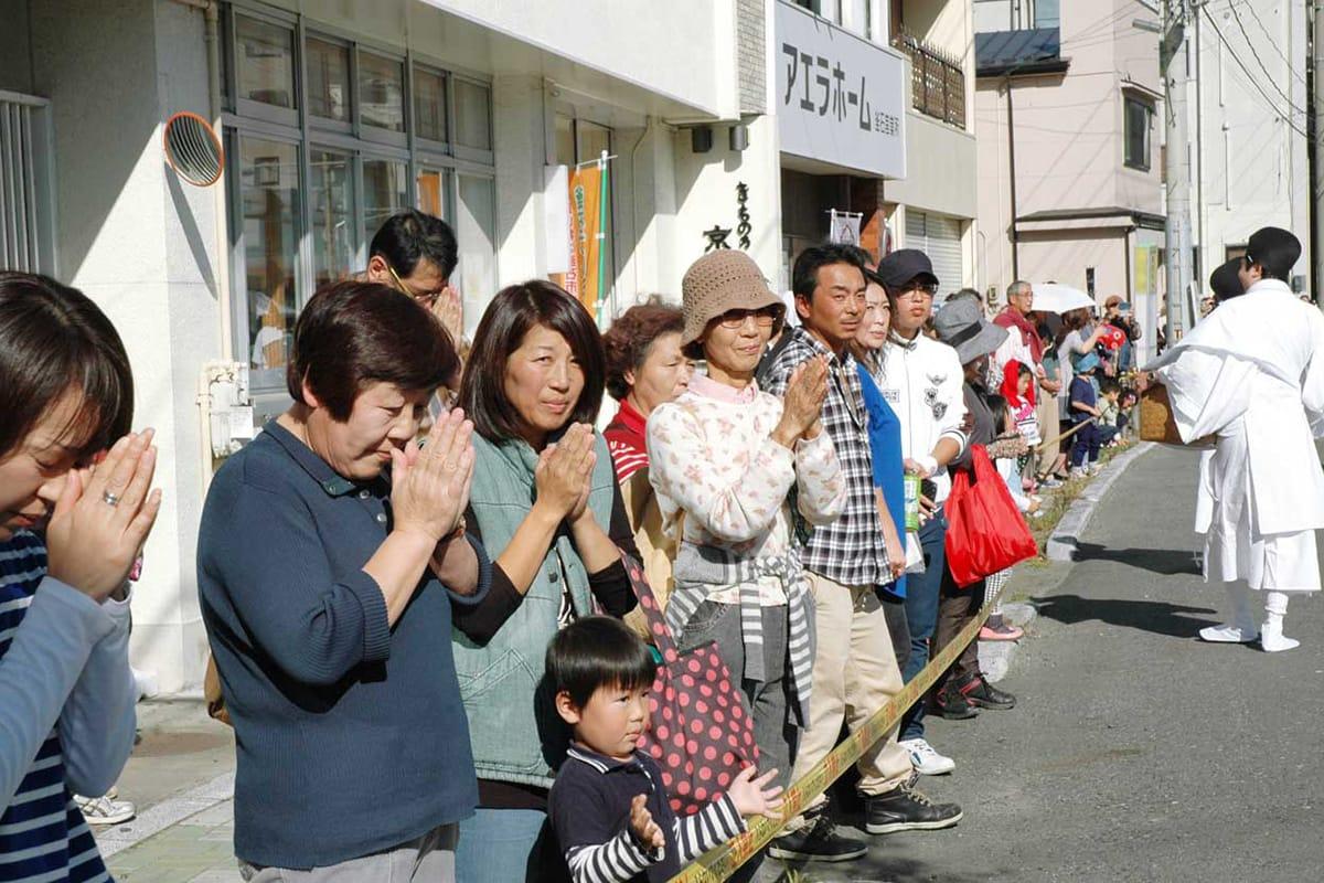 目抜き通りを練り歩くみこしに手を合わせる見物客=大町