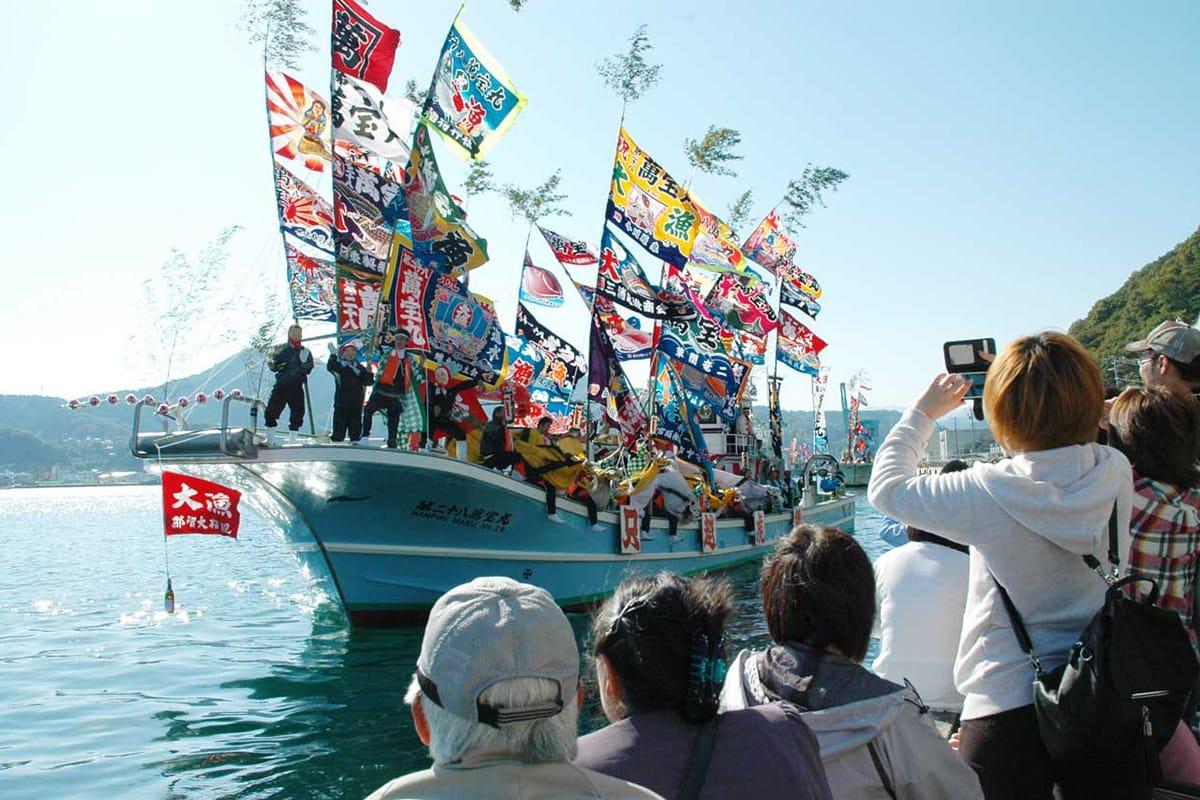 秋晴れに恵まれた曳き船まつり。青空に色とりどりの大漁旗が輝く