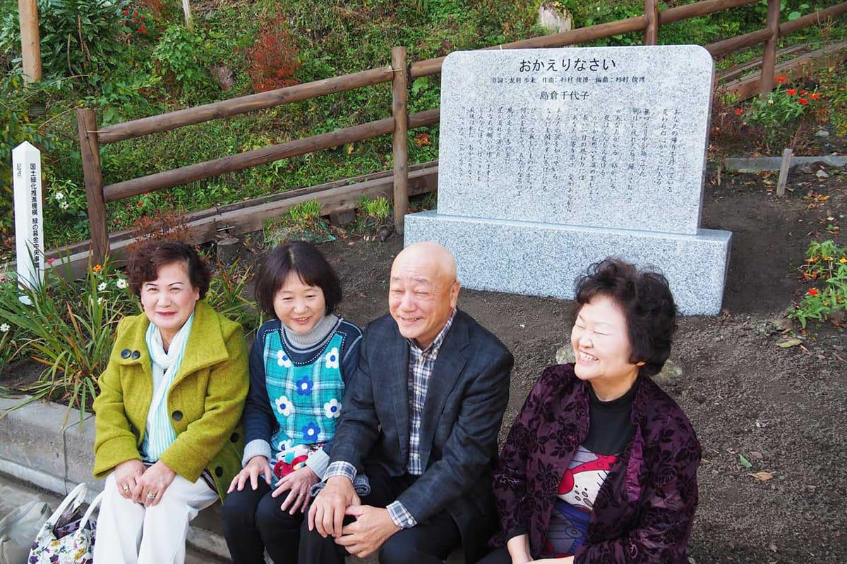完成した歌碑の前で笑顔を見せる佐野さん、吉田代表、小松義次さん、西さん(左から)