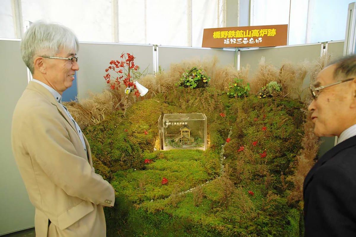 すべて自然の植物でつくりあげた「橋野鉄鉱山高炉跡」のジオラマ。「今こそ取り上げねば」と浅利事務局長(左)