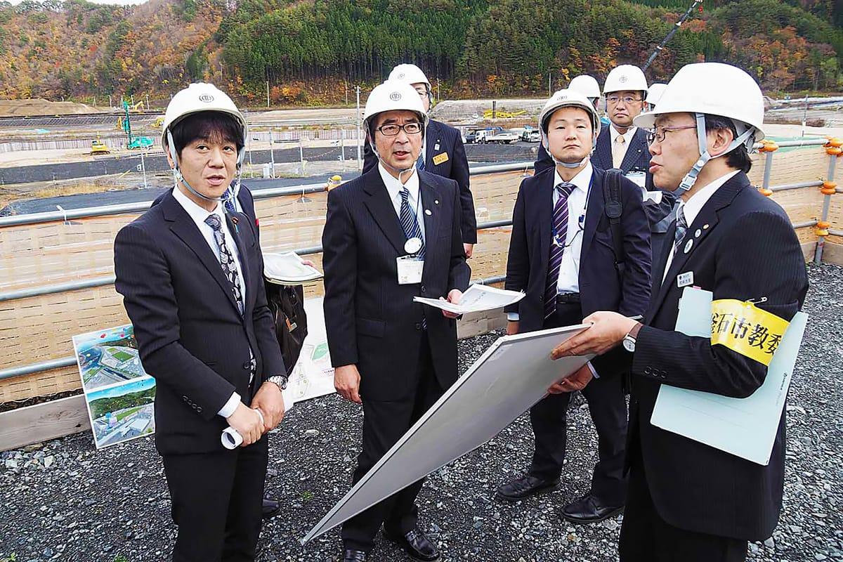 鵜住居地区の学校建設現場で説明を受ける義家副大臣(左)