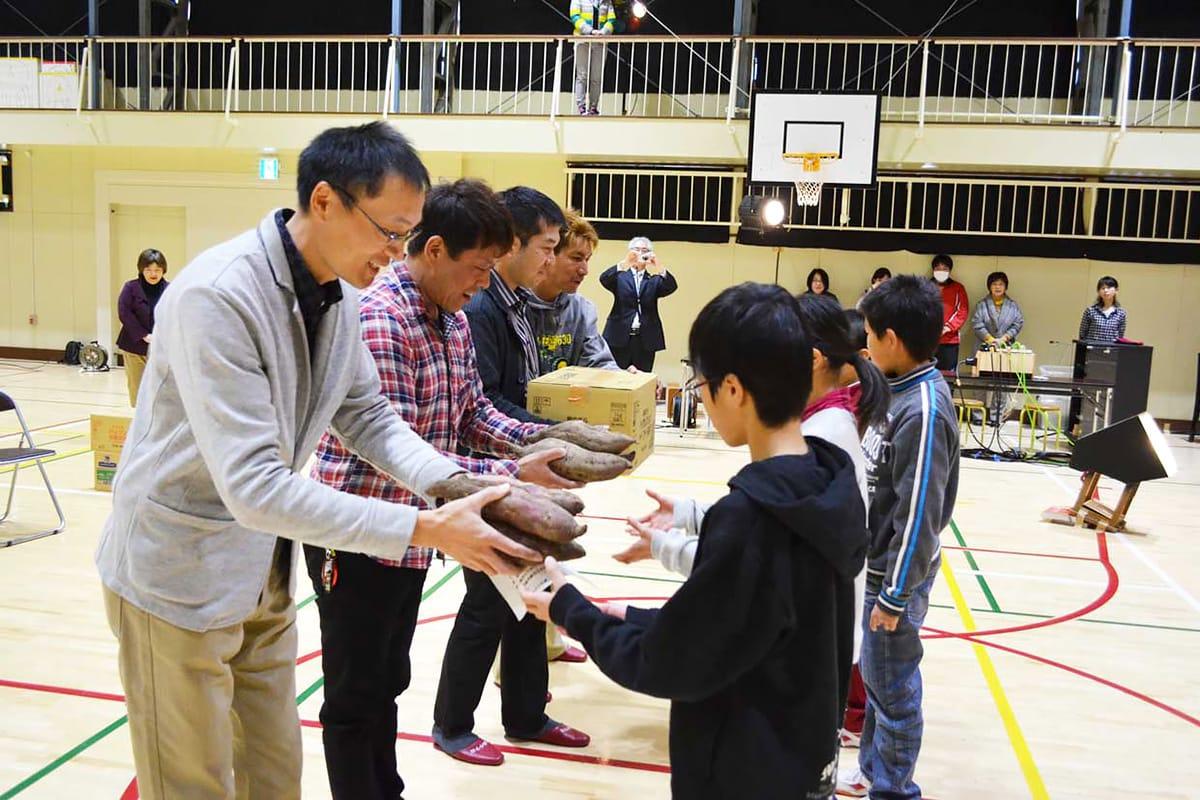 白山小児童にサツマイモを贈る飯島地区青少年育成会の4人