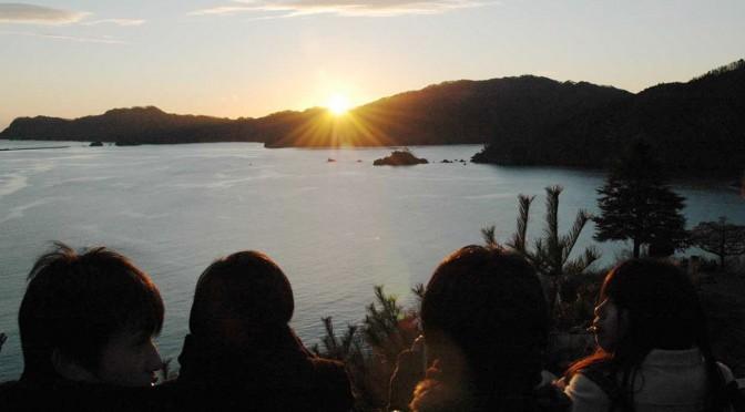 待ちわびた初日の出に手を合わせ、写真に収める初詣客=元日午前7時2分
