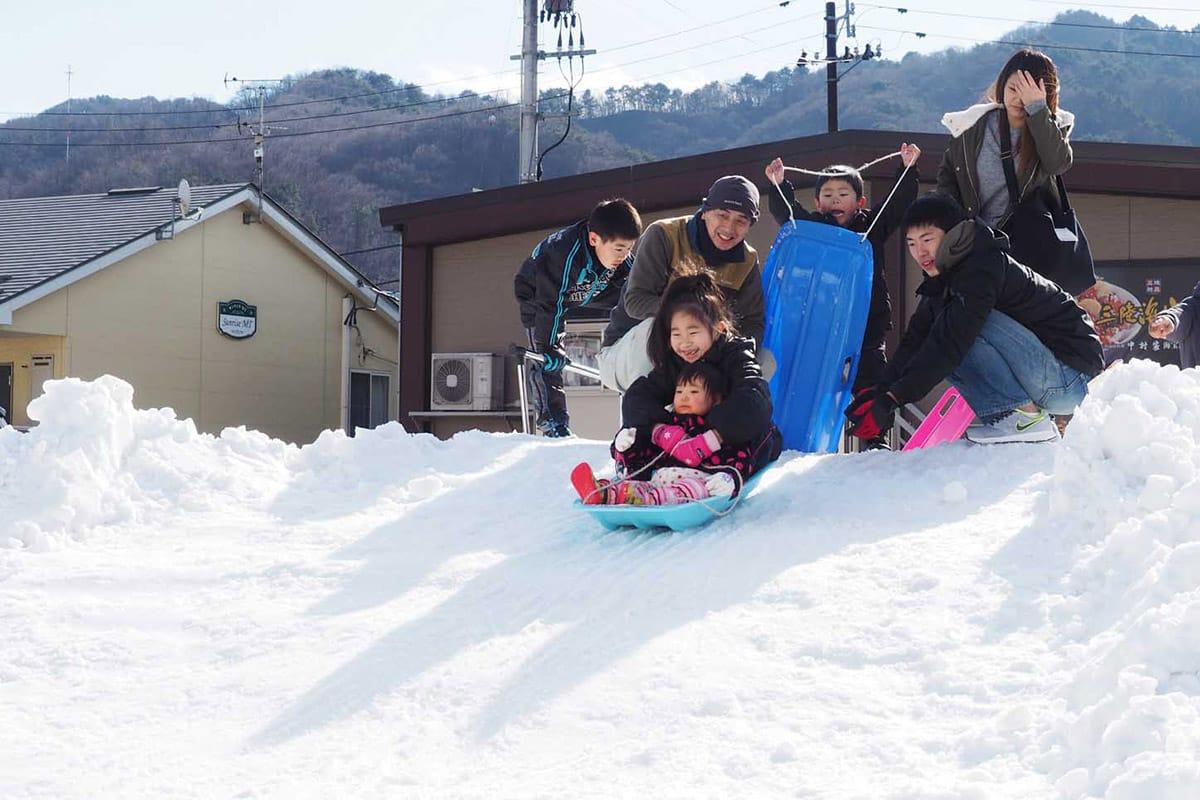 雪の滑り台は今年も大人気。雪遊びを楽しむ子どもたちの笑顔でいっぱい