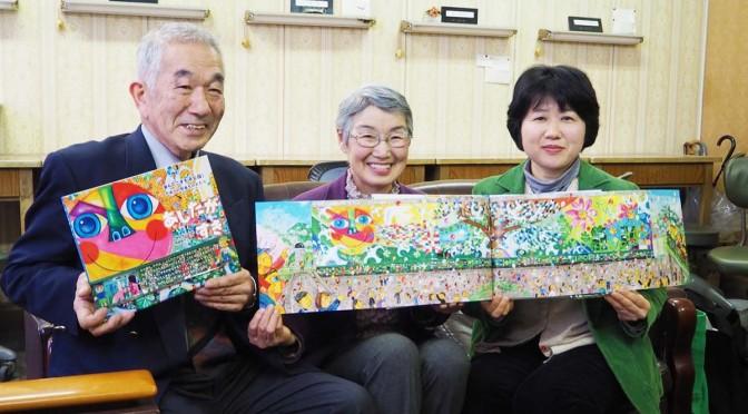 完成した絵本を手にする藤井了さん、妻のサエ子さん、作者の指田和さん