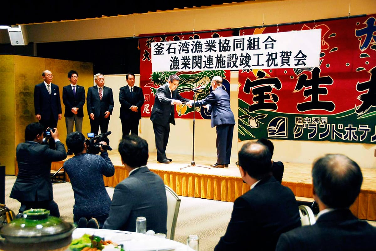 釜石湾漁協漁業関連施設の復旧完了を記念する祝賀会で工事業者らに感謝状を手渡す細川組合長