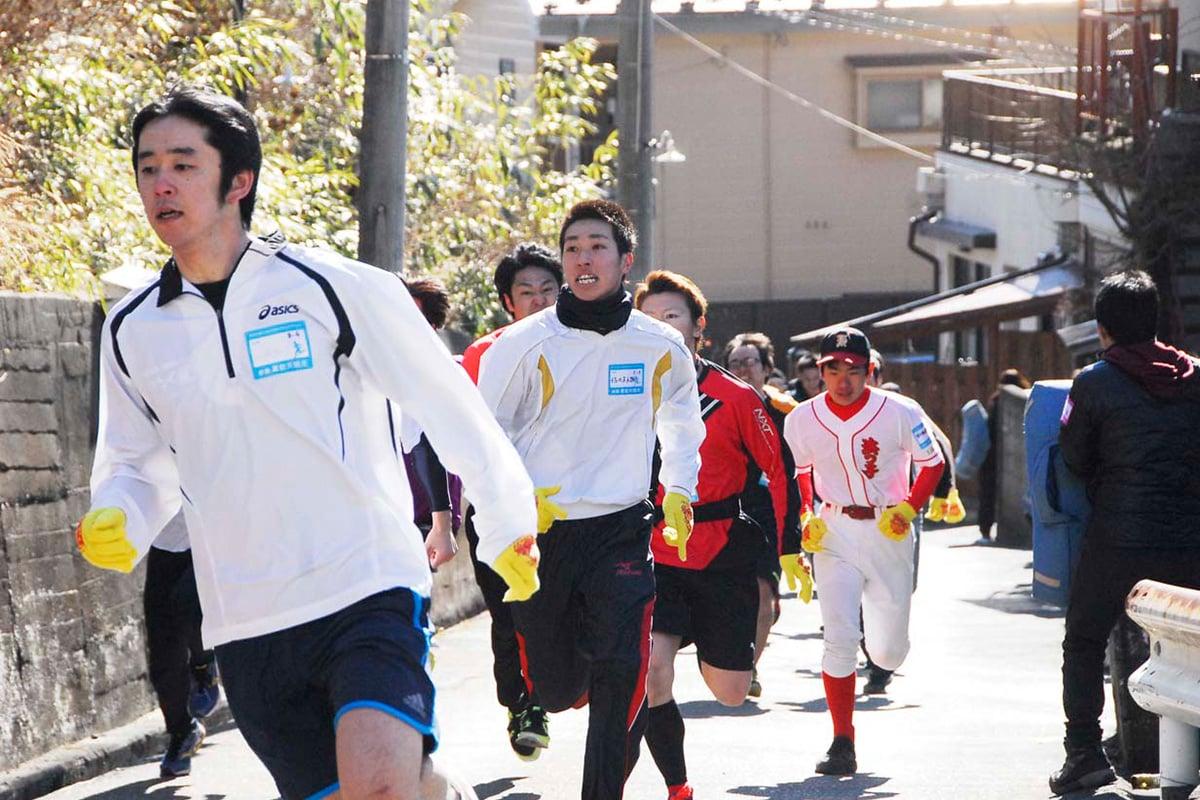 急坂を全力で駆け上がる「男性29歳以下の部」の参加者