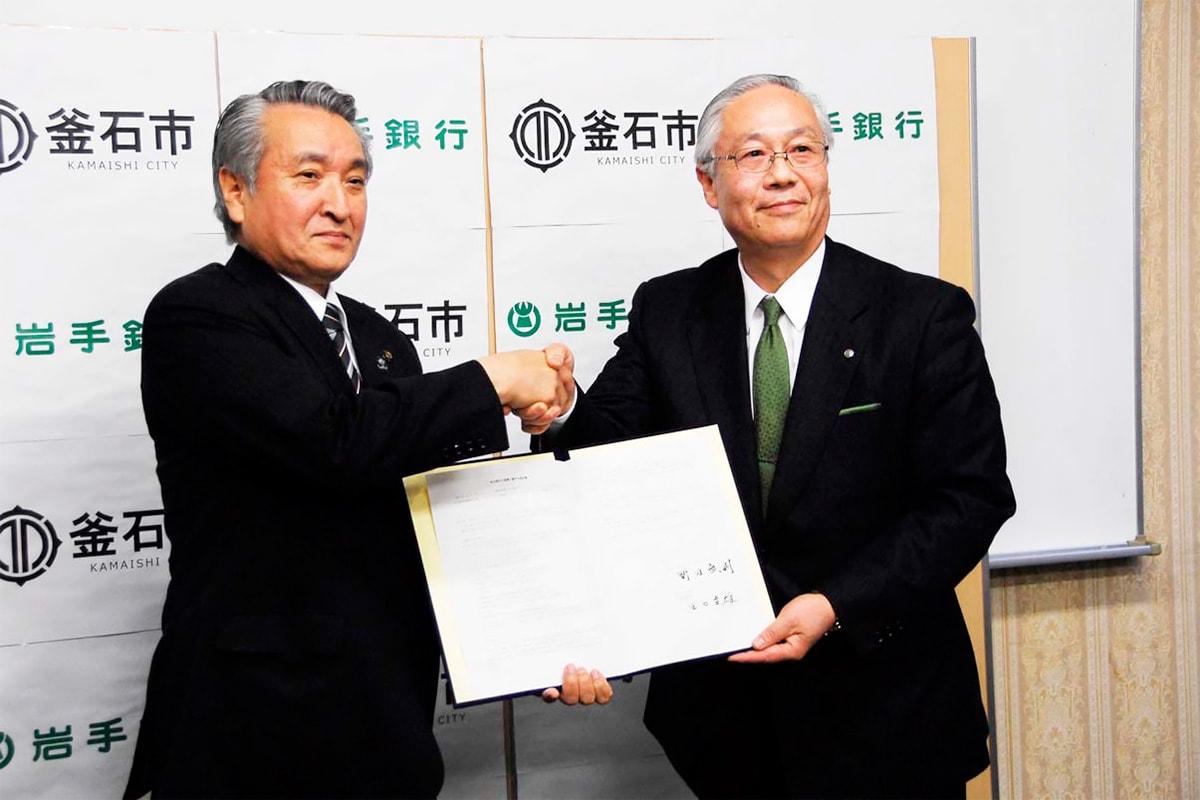 協定書に署名し握手を交わす田口頭取(右)と野田市長