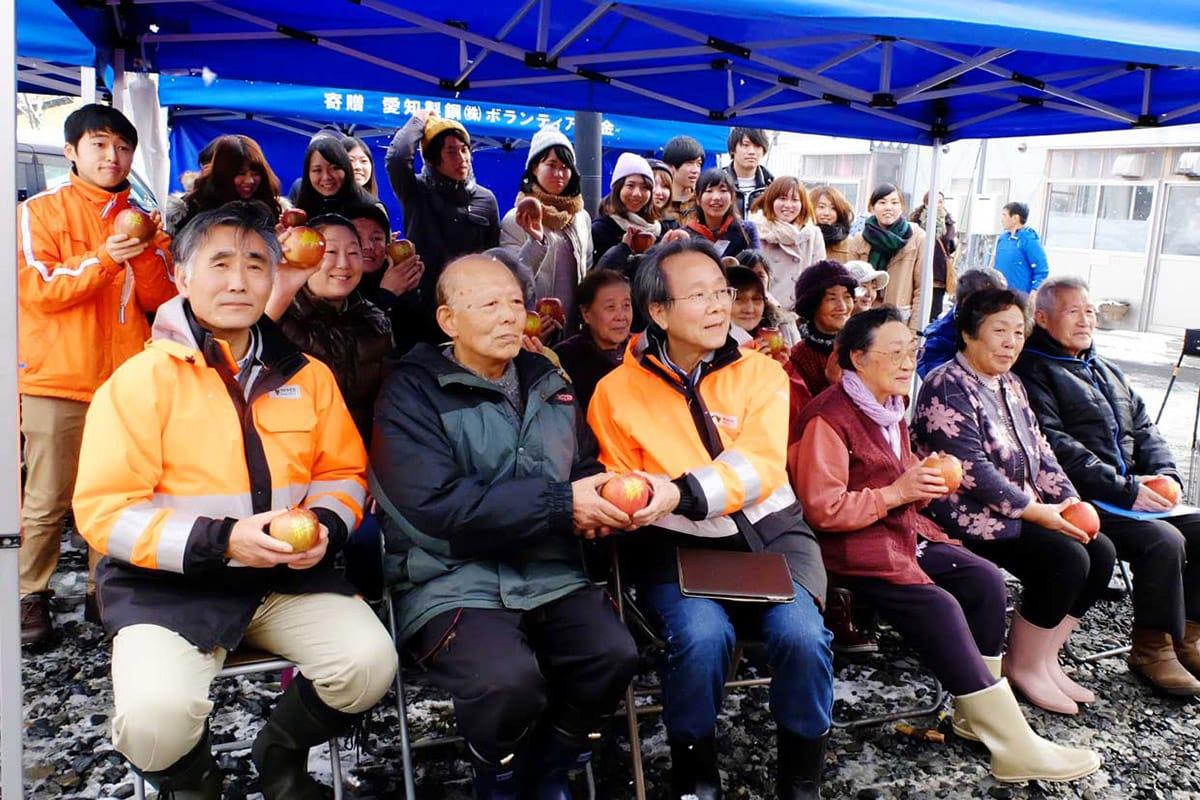 「絆」と刻まれた復興リンゴを手に記念撮影する自治会長の萬さん(前列左から2人目)