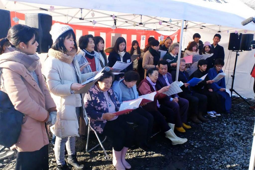 支援の学生らと合唱を披露する仮説住宅の住民ら