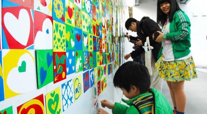 製作したマグネットシートを壁に貼る子どもを笑顔で見つめる寺崎幸季さん(右)