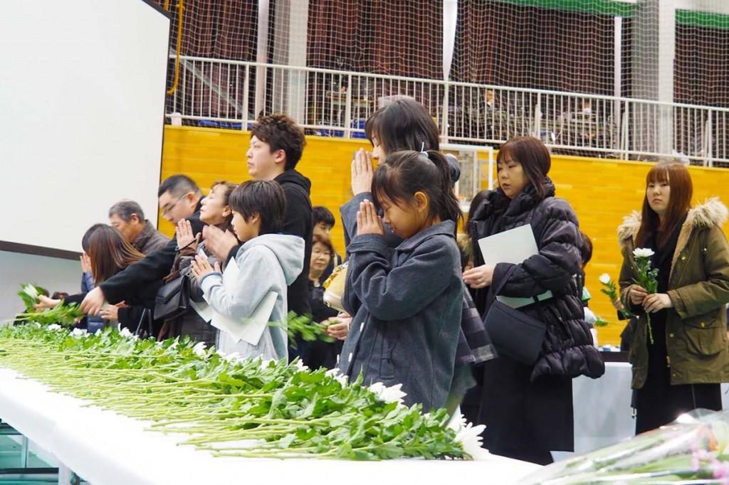 釜石市主催の震災5周年犠牲者追悼式で、犠牲になった家族や知人の面影を思い、手を合わせる参列者=11日釜石高校体育館