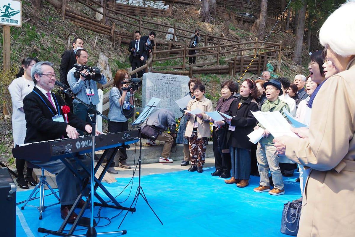 集まったファンらは完成した歌碑の前で歌声を合わせた