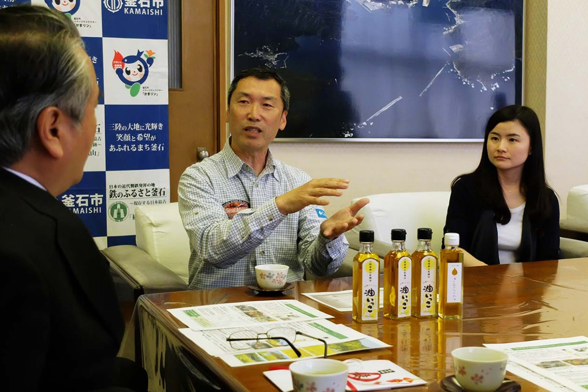 菜種油「油いっこ」を前に思いを語る山田代表(中)