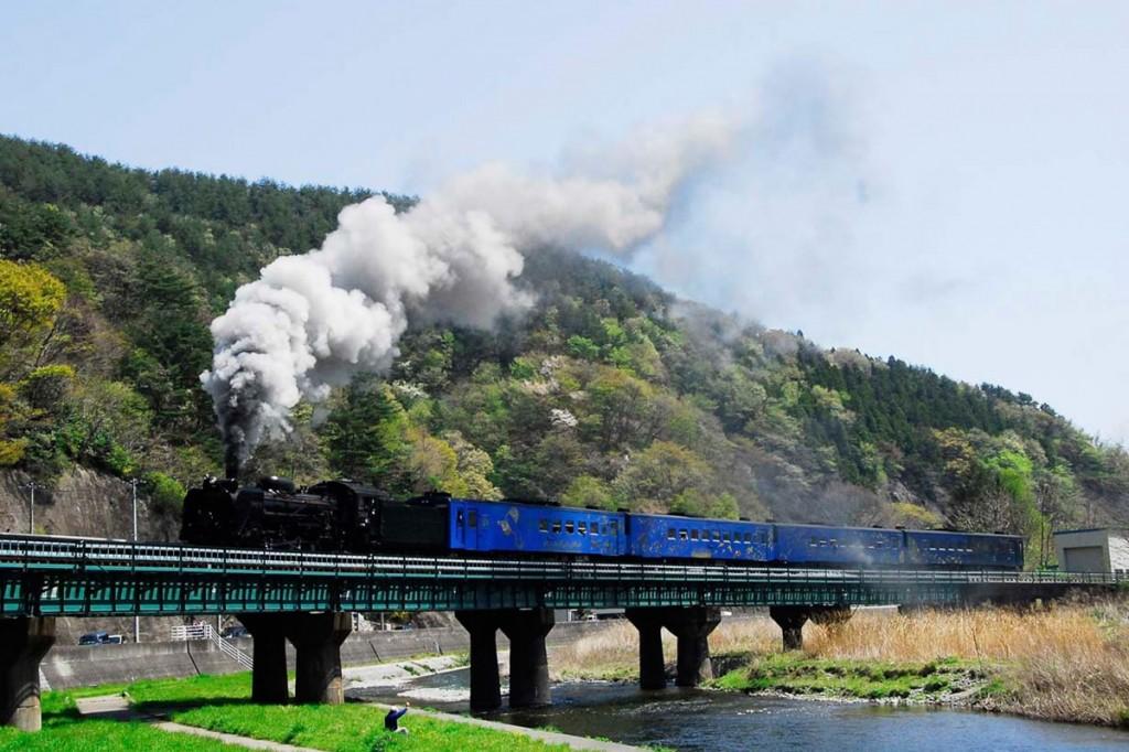 新緑をバックに煙を吐きながら鉄橋を進む「SL銀河」