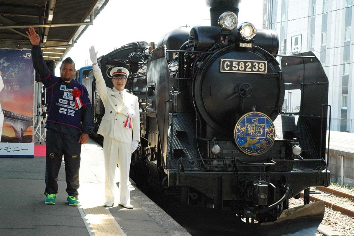 楽しいSLの旅を願い出発合図をする角谷駅長とマヘ選手