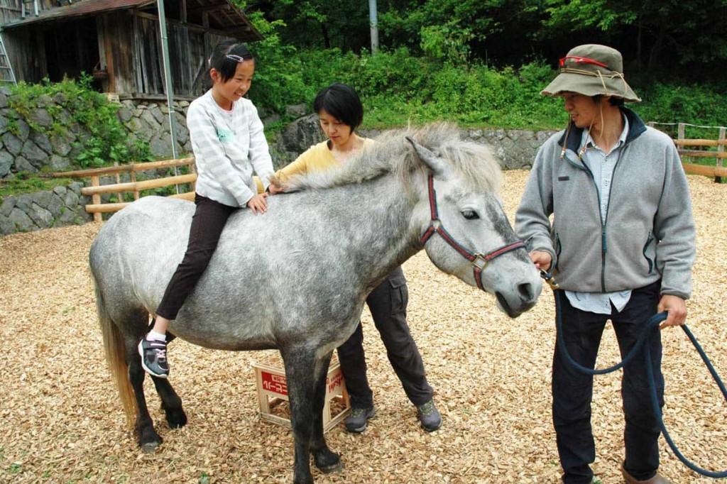 黍原豊さん(右)が引く馬に乗り、何ともいえない心地良い感覚に身をゆだねた乗馬体験