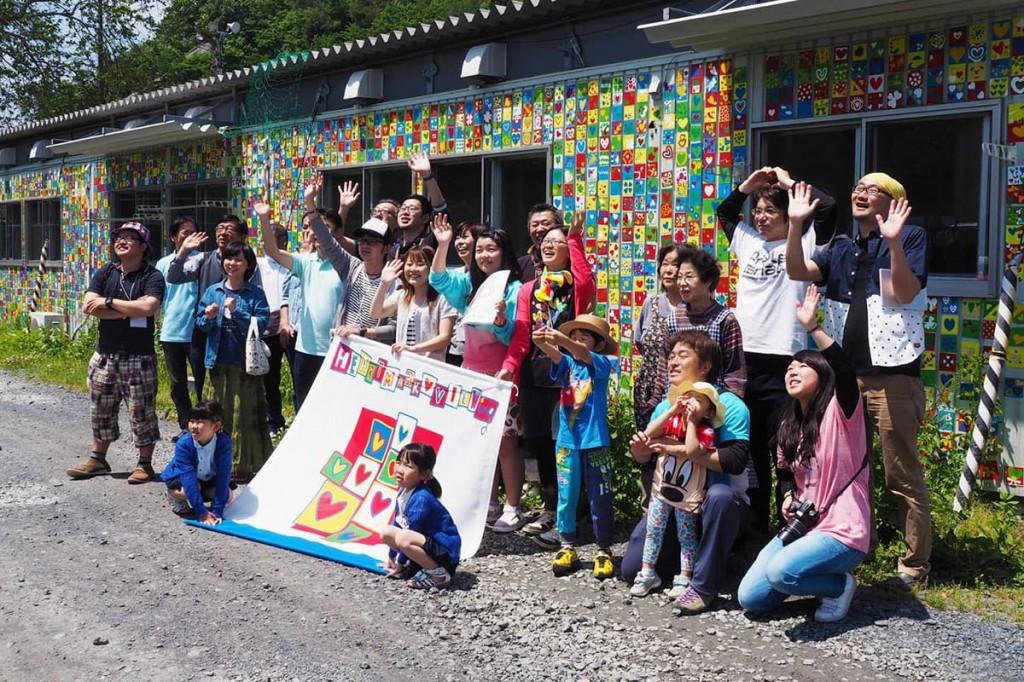 作業前にハートのマグネットで彩られた仮設住宅の前で記念撮影する参加者