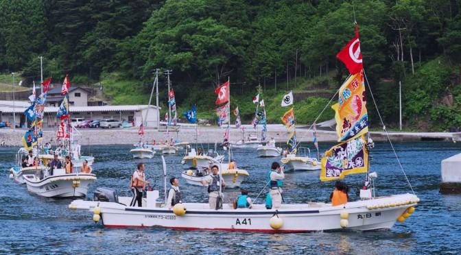 大漁旗をはためかせた漁船で海を回り、復興完了を祝った