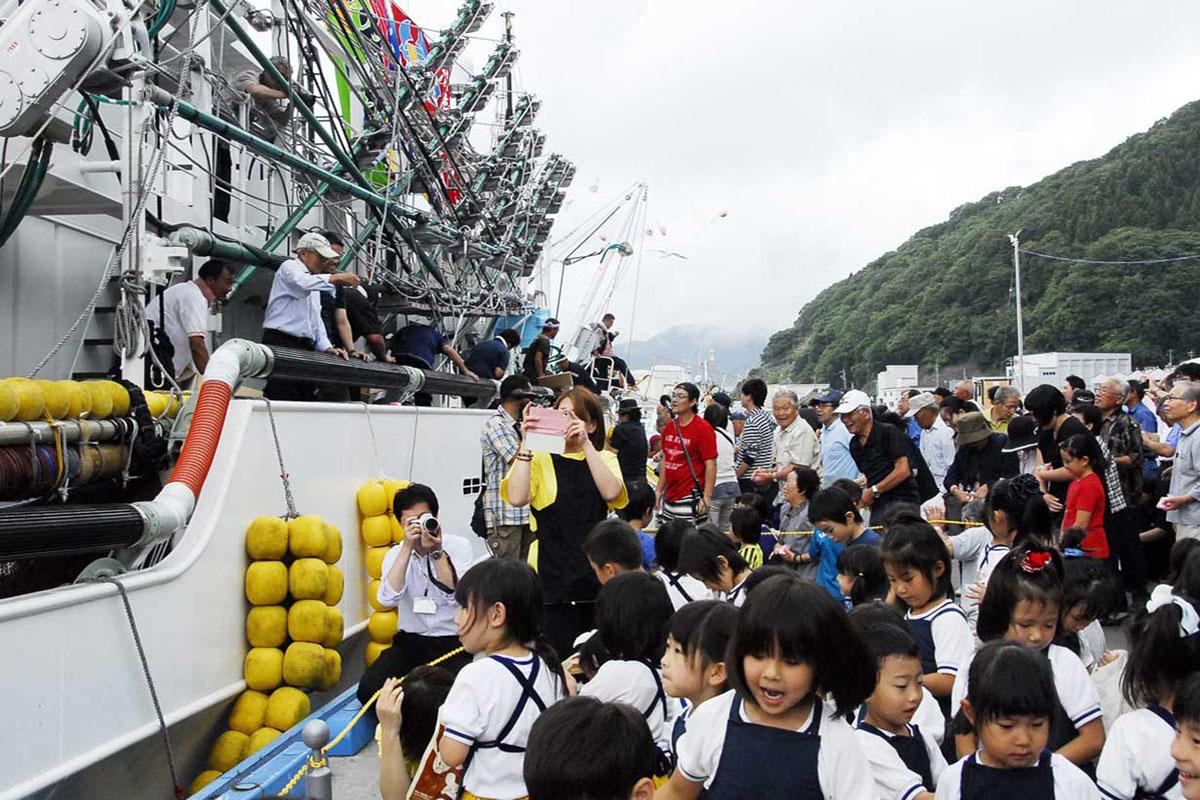 餅をまき出漁を景気付ける浜川社長ら
