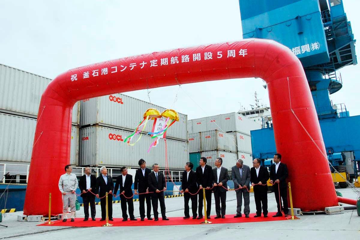 くす玉を割り、釜石港コンテナ定期航路5周年を祝う関係者