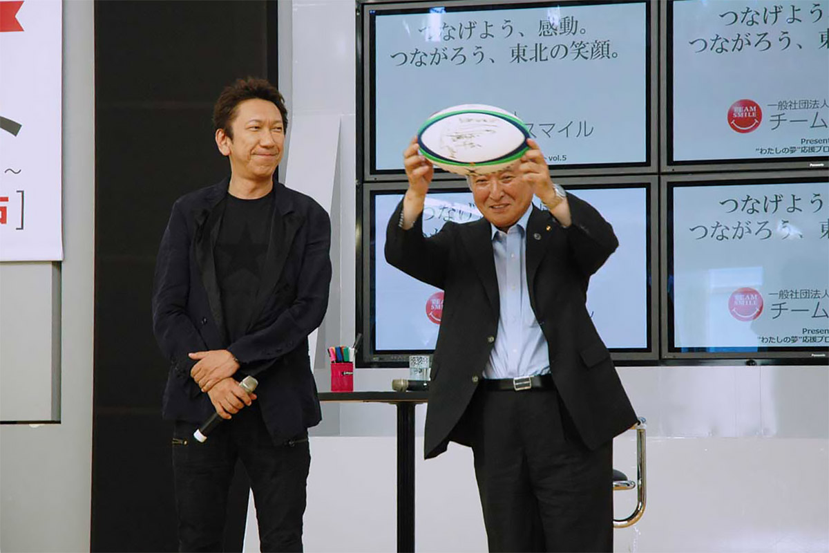 トークショーを行った布袋寅泰さんと布袋さんのメッセージ入りサインボールを掲げる野田武則市長