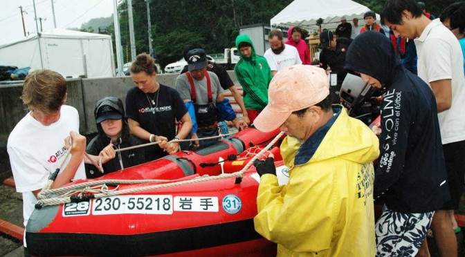 神事の後、救命艇を海に運ぶ関係者。開校式に続き、さっそくスクールの講習がスタートした