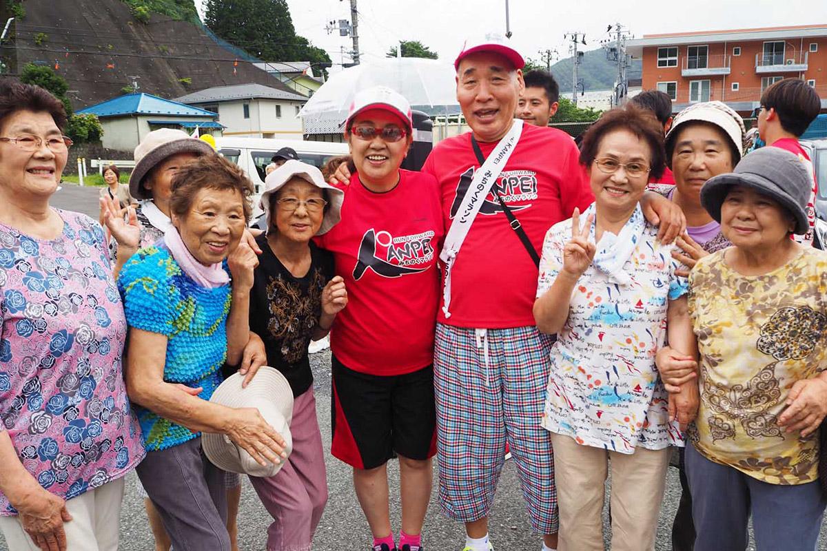 天神町仮設団地で住民と触れ合った宮川大助・花子さん(中央)