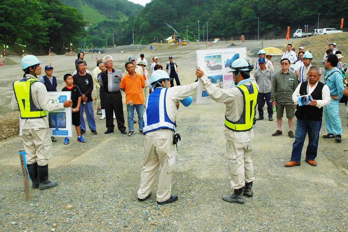 工事担当者から説明を受ける見学会の参加者ら