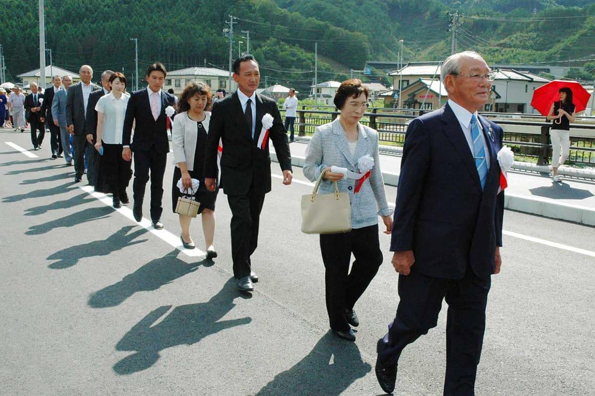 吉平さん(右)を先頭に長内橋の渡り初めをする岩﨑さん一家