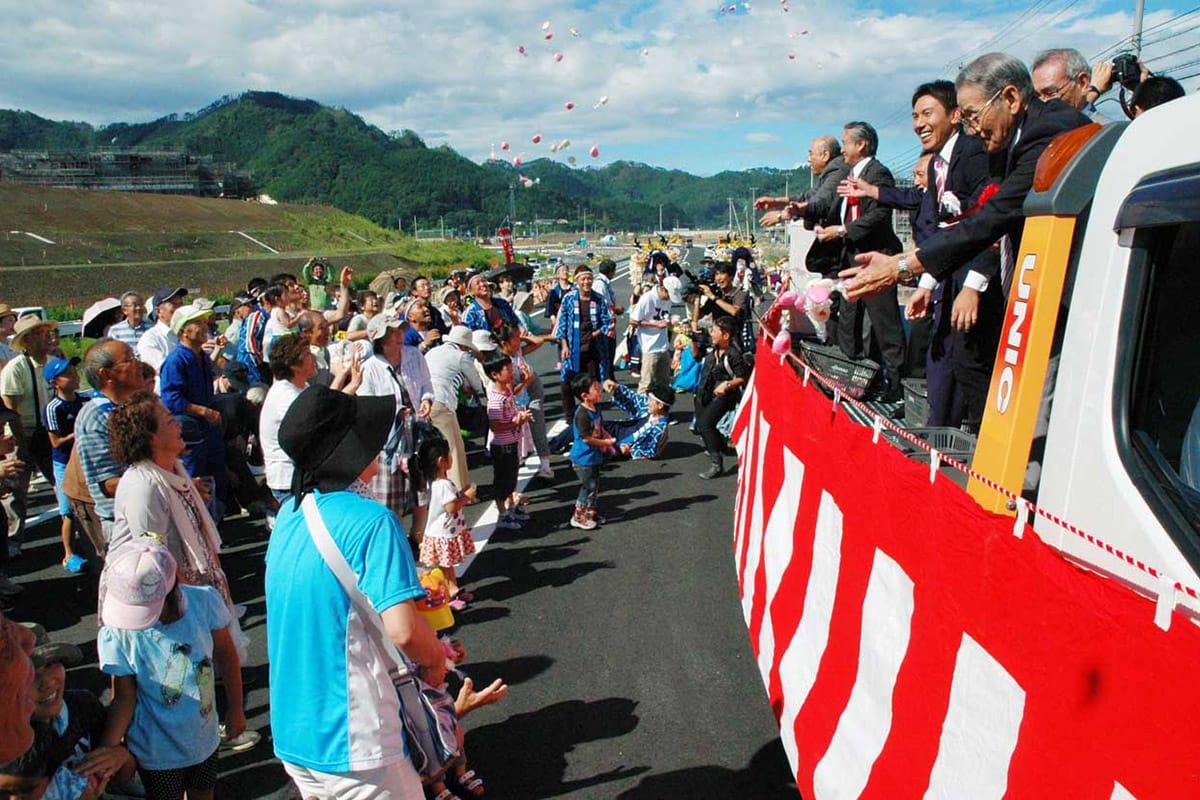 餅まきに笑顔を広げ、新国道の開通を喜ぶ地域住民ら