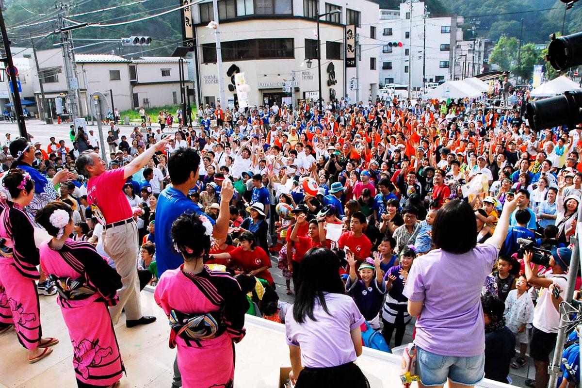 威勢よく餅まきで28回目の「釜石よいさ」の幕開け。特設ステージの前に大勢の市民が群がった