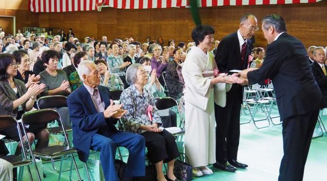 市主催の敬老会で、長寿のお年寄りに祝い金を贈る野田市長