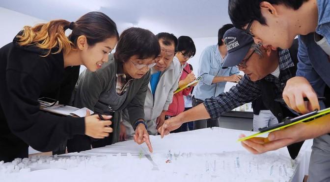 細かく復元された模型を指さしながら学生に建物の名称などを教える住民たち