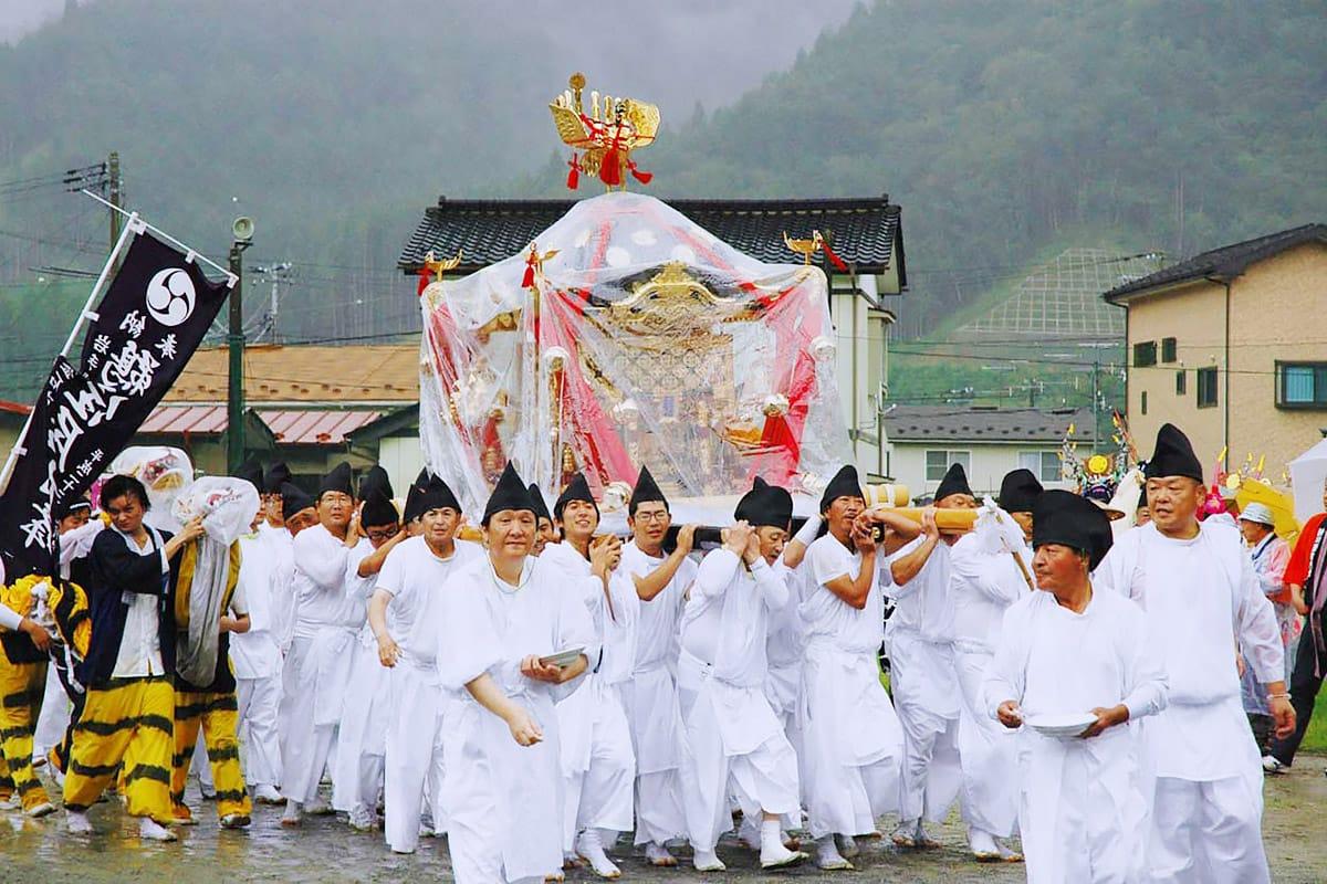 降りしきる雨の中、日向グラウンド内を練り歩く鵜住神社のみこし=18日昼前