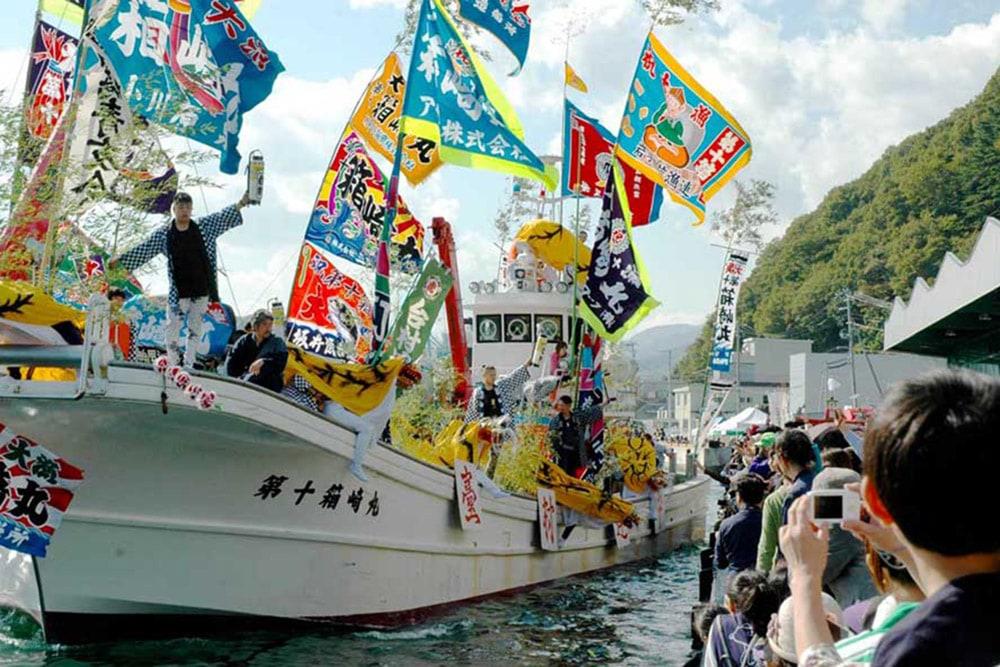 秋の日差しに輝く色とりどりの大漁旗が美しい曳き船まつり
