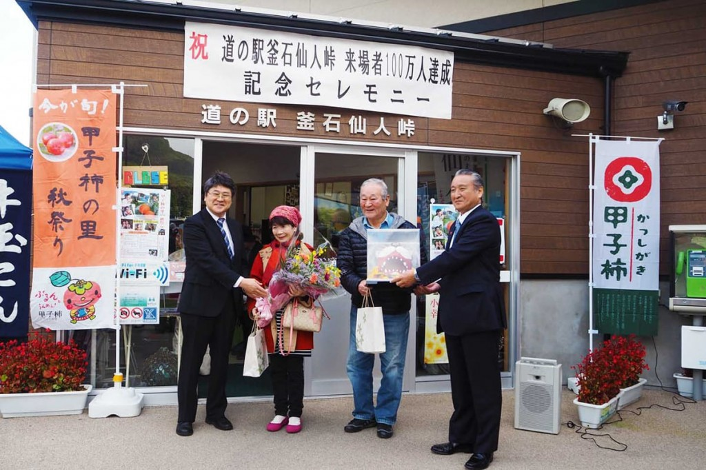 来場者100万人目となり、記念品を受け取る花井英夫さん夫妻(中央)