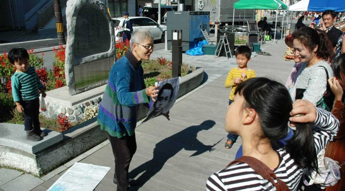 """青葉通りの""""啄木歌碑""""の前で、上田初子さんから啄木の旅について話を聞く参加者"""