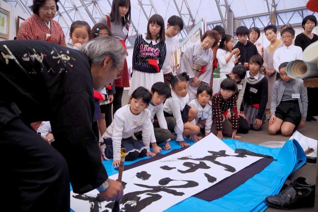 「釜南44」による書とのふれあい体験に子どもたちは興味津々
