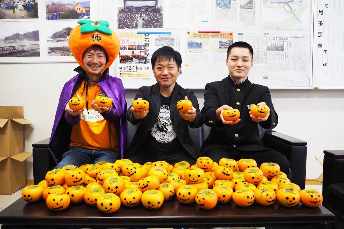 柿を手に笑顔を見せる(左から)関谷さん、三浦さん、沼﨑君