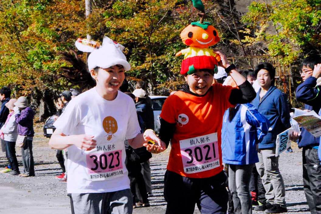 かわいい甲子柿の帽子をかぶり、笑顔でゴールに入る女子ランナー
