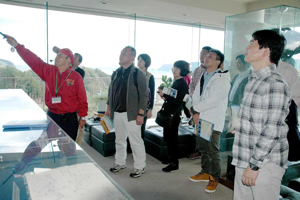東日本大震災津波の陸地への到達を遅らせた湾口防波堤について説明を受けるJATAの会員ら=鉄の歴史館で