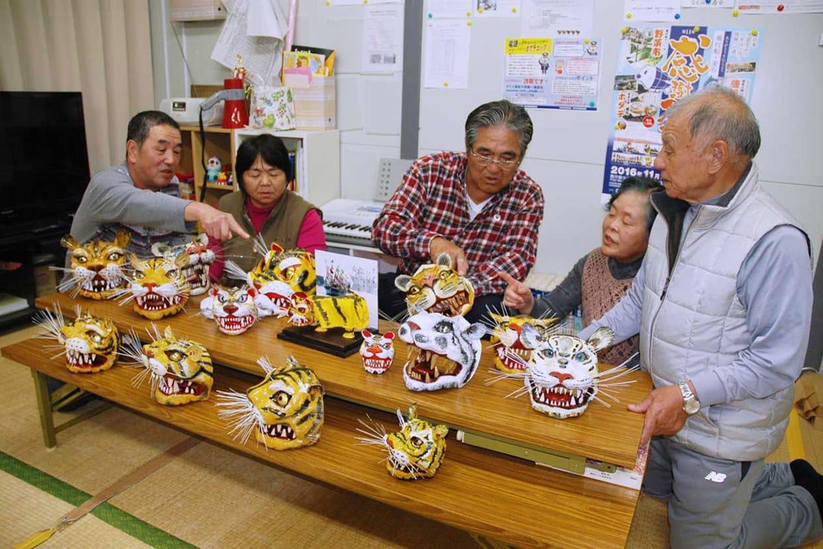 苦労を重ね、ついに完成させた虎頭を鑑賞しながら会話を弾ませる桜木町仮設団地の住民ら