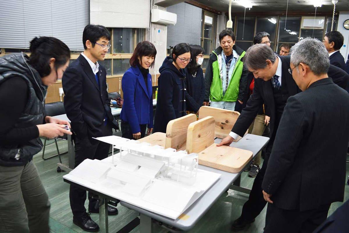 メーンスタンドのイメージ模型と木製シートのサンプルに見入る委員ら参加者
