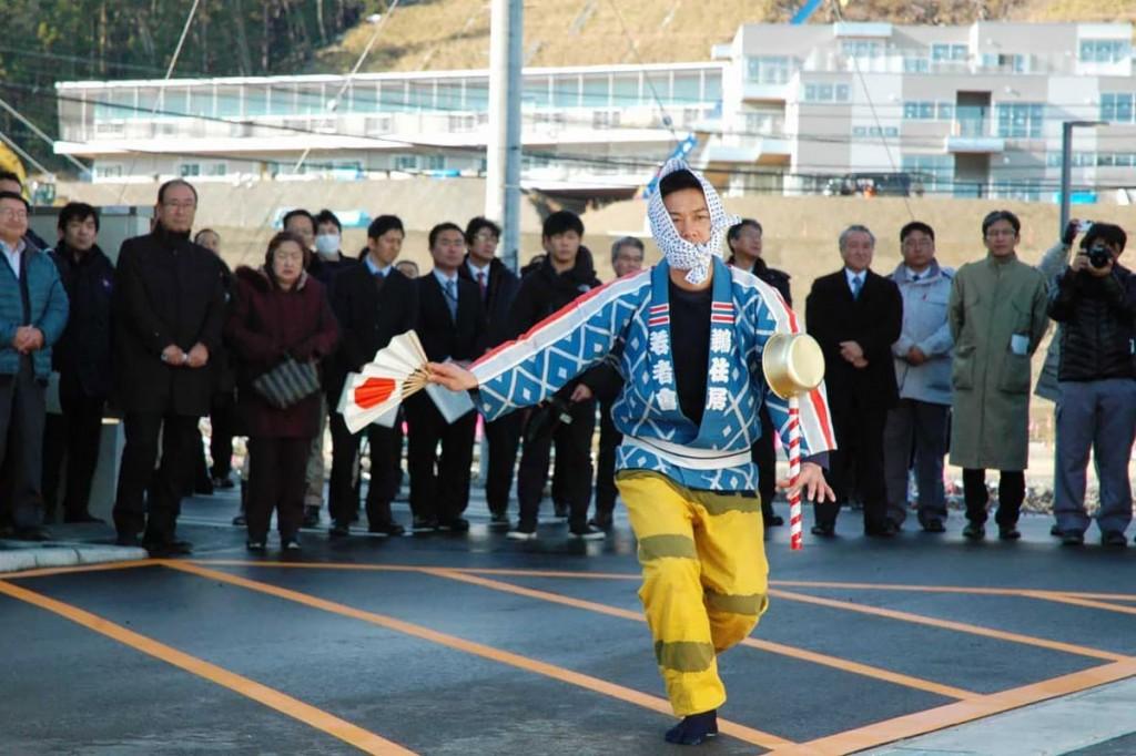 竣工を祝い鵜住居虎舞の手踊り。背後には完成間近の学校校舎も
